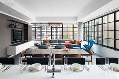 Workshop/APD Brings an Artsy, Urbane Touch to an Apartment Overlooking New York City's High Line | As seen from the island kitchen, the dining/living area is anchored by a wall of custom gray-stained fumed white oak; Jason Miller's Mini Endless Double pendant light in glass and stained oak illuminates a custom walnut-slab dining table by Tyler Hays. #design #interiordesign #interiordesignmagazine #projects #cityapartments