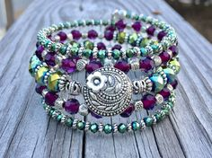This 5 coil bracelet is made with stainless steel memory wire - will adjust to the size of your wrist and no chance of breaking. This will ensure you will have this bracelet for a long time. Materials include 4 and 8mm Faceted peacock Czech glass crystal beads, 6mm deep purple Faceted glass crystal beads paired with an assortment of Tibetan silver spacers and a decorative flower design button in the middle of the center coil. The button measures 3/4 in diameter. Finished off with matching…