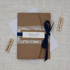 Your guests will adore these rustic inspired navy blue and lace pocketfold wedding invitations. Crisp white paper on simple brown card.