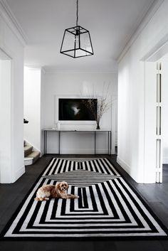Monochrome entryway: black timber floorboards, black and white geometric-pattern rug/runner, white walls, modern black and glass pendant light