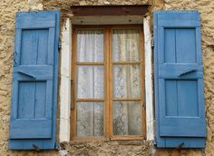 Blue shutters and lace curtains