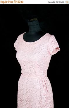 Feminine 1950s dress is made out of a nice sturdy cotton pink lace lined in acetate. Dress is form fitting and very flattering. Simple but sweet, this has a few pleats at one hip asymmetrically to add some extra interest. This has short sleeves and zips up the back with a metal zipper. -Measurements- Bust: 36 inches Waist: 26 inches Hips: 40 inches Length: 40 inches Condition: Excellent, freshly washed.  ☞ Social media for Garb-Oh Vintage  https://www.instagram.com/garb_oh_vintage…