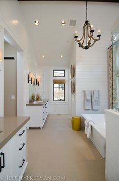 Bathroom. The vaulted bathroom has beautiful hanging chandelier, the walls are covered in painted tongue and groove cedar paneling. #Bathroom