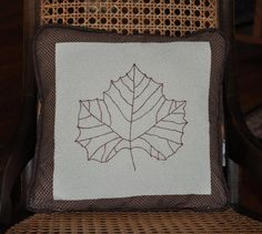 Hand-made in the Catskills by Millions of Stitches.  The maple leaf on this striking pillow is hand embroidered. The covered cording and back are a complimentary brown fabric which has a marbled look. The three fabrics are high quality and really compliment one another.    Millions of Stitches will be at the Maple Weekend holiday pop-up farmers' market at the Delaware Inn on 3/16/2013.    This is a beautiful accent piece