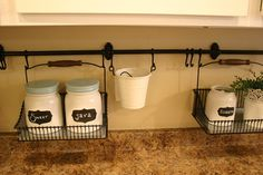 Noticing her counter was getting too full, blogger Christina took advantage of wall space. She installed a railing and hung baskets and caddies off of them. In them, she placed labeled jars and decorative flowers, converting her empty backsplash into a beautiful, Pinterest-approved wall organizer.