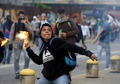 Un manifestante lanza un cóctel molotov, mientras enfrentándose con la policía antidisturbios durante una manifestación contra el gobierno del presidente de Venezuela Nicolas Maduro en Caracas.  REUTERS / Carlos Garcia Rawlins