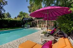 Hot pink umbrellas line the pool deck to provide shade from the sun, while cushioned chaises in shades of orange and olive green offer a spot for sunbathing.