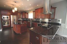 """Who wants to cook a meal in this extra-large chef's kitchen w/ 36"""" cooktop & island hood, large island & peninsula w/ additional seating?  #RomanRealty"""