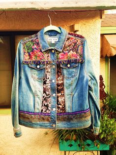 Boho style denim jacket with peace sign and flowers painted on the back. Various thrifted fabrics and trims hand sewn on jacket. Size: Womens XL Care Instructions: For longevity of fabric paints we suggest you spot clean. For more creations check us out on Instagram @bleudoor