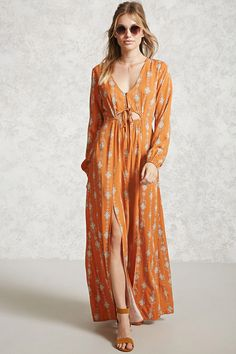A woven maxi dress featuring an allover ornate print, scoop neckline with a button closure, a self-tie with a cutout front, long sleeves with elasticized wrists, an M-slit front, and an elasticized waist.