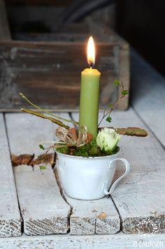 petite tasse décorée de feuillage, fleurs naturelles ou de soir et agrémentée d'une chandelle