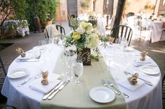 Crisp white linens with a sage green table runner and wildflower arrangement. Janae Shields Photography.