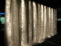 White Christmas lights suspended from ceiling with magnets and covered up with either white gossamer or doubled up white tulling.