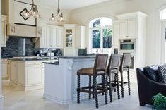 Traditional feel to this modern white cabinets kitchen is brought by maticulous details like architectural elements of furniture, arched window and olde-style dark bar chairs. Spectacular navy backsplash serves as  focus, complete with traditional chandeliers.