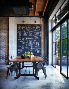 Do rústico antigo para o contemporâneo: cimento queimado, cadeiras de ferro, pé direito alto, tijolos aparentes e quadro/lousa compõe essa sala de jantar com uma luz natural incrível.