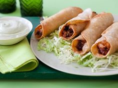 Chicken Flautas with Avocado Cream - Roll up timesaving, spiced-up rotisserie chicken and cheese inside flour tortillasand fry for an easy, crispy summer appetizer best dunked in lime-spiked avocado cream.