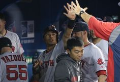 TORONTO, CANADA - AUGUST 26: Mookie Betts #50 of the Boston Red Sox is congratulated by teammates in the dugout after scoring a run in the eleventh inning during MLB game action against the Toronto Blue Jays on August 26, 2014 at Rogers Centre in Toronto, Ontario, Canada. (Photo by Tom Szczerbowski/Getty Images)