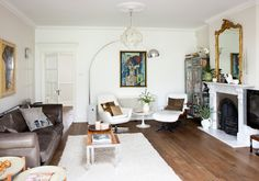 white walls, gold gilt mirror, white rug modern twist, ugly wall art and couch