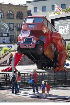 "A 1957 double-decker bus is doing push-ups. The ""London Booster"". Czech sculptor David Cerny's creation has mechanical arms, windows made from television screens, and an engine that allows it to move up and down."
