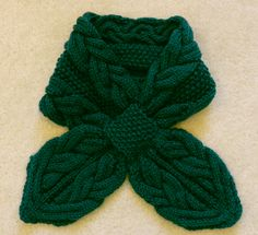 Soft and sophisticated, this Rainforest Cables scarf is the perfect romantic accessory to add to your wardrobe. Hand-knit in Aran-style cables and seed stitch, this ascot-styled scarf is the perfect accessory for winter. Its rich forest green color and stylish pattern, turn even the most casual outfit into elegant attire.