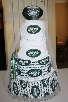 Jets Diaper Cake. $125. J-E-T-S...Jets! Jets! Jets! themed diaper cake: Top layer Jets infant bib with soft Jets football adorned. 2nd layer: Jets onesie. Tier 3:hand made Jets larger bib with wipes case with 16 Huggies Natural Care wipes on side. 3rd layer: burp cloth. Tier 4 Jets burp cloth. All layers have football printed ribbon. Approx 100 pampers in the size of your choice.