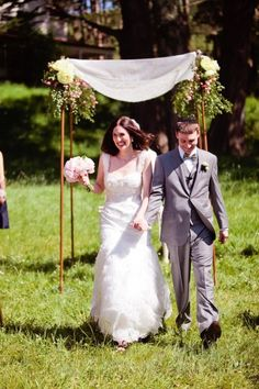 chuppah - simple wood pole chuppah with minimal decorations on the top and also at the baes