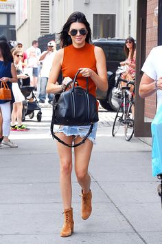 Kendall Jenner wears an orange tank with a distressed denim mini-skirt, a black leather bag, brown lace-up boots, and sunglasses
