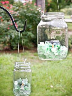 Create Glass Lanterns for the Backyard using mason jars, sea glass, tea lights & wire.