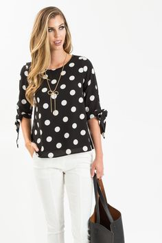 Polka dots and ribbon tie sleeves, what more could a girl ask for? We love this feminine blouse and its chic black and white print! This blouse is great for wearing over jeans for a casual and comfy e