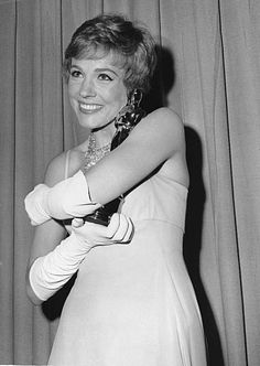 """Julie Andrews hugs the Oscar that she won for best performance by an actress for her role in  """"Mary Poppins"""" at the Academy Awards in Santa Monica, Calif., on April 6, 1965. (AP Photo)"""