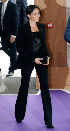 Why Queen Elizabeth Isn't a Fan of Meghan Markle's Power Pantsuits - - The Duchess of Sussex often wears pants for her official outings, but it doesn't have the royal seal of approval. Estilo Meghan Markle, Meghan Markle Stil, Meghan Markle Legs, Meghan Markle Photos, Style Année 20, Her Style, Markle Suits, Outfits Pantalon Negro, Work Fashion