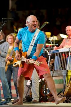 Jimmy buffett.i love the shirt he is wearing.i love that blue color.and those shorts are cool too.i am so looking foward to late spring and summer when i can wear a pair of shorts and a tee shirt.