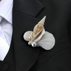 "This fun seashell boutonniere is a perfect accent for the groom's jacket at a beach-themed or seashell wedding. The boutonniere is real shells with white pearls and has a pin in the back. Size: 2.75""."