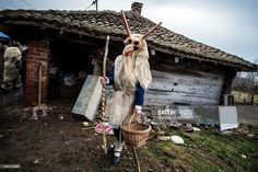 A child wearing a mask stands in front of a house during 'Bele Poklade' carnival celebrations in the village of Lozovik, some 100 km (62 miles) south of the capital Belgrade, on February 22, 2015. 'Bele Poklade' has its roots in old pagan customs and is marked annually seven weeks before Easter. Children walk through the village to collect eggs, and at the end jump over a fire to banish evil demons.