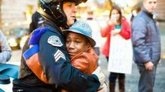 "PORTLAND, OR — It's the picture we needed to see after a week like this.  A 12-year-old black boy, tears streaming down his face, and a white police officer embrace in the middle of a Ferguson-related demonstration in Portland, Oregon.  The boy, Devonte Hart, was holding a sign offering ""Free Hugs"" during a Tuesday protest over a grand jury's decision not to indict Ferguson police Officer Darren Wilson"