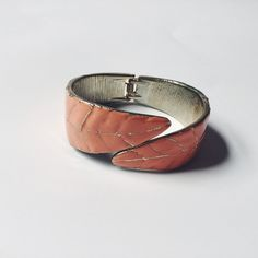 Leaf bracelet cuff Peach colored leaf bracelet cuff. It has a hinge closure and measures about 2.5 inches in length. Jewelry Bracelets