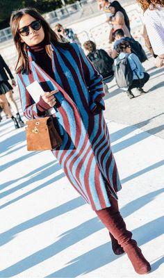 Miroslava Duma in a blue and burgundy coat and brown suede purse