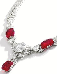 AN ART DECO PLATINUM, RUBY AND DIAMOND NECKLACE, CIRCA 1920. Of geometric design, the front set with three cushion-cut rubies weighing 8.60, 8.48 and 5.99 carats, centred by an old European-cut diamond weighing approximately 8.80 carats, accented by six old mine and old European-cut diamonds weighing approximately 6.70 carats, further set with numerous old mine, old European and single-cut diamonds weighing approximately 26.00 carats,length 17½ inches. #ArtDeco #necklace