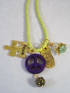 Satin lime green cord 18. in. With purple peace sign and charms. Very cute!