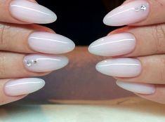 Smalto rosa bianco con applicazione di brillantini sul dito anulare per una manicure perfetta