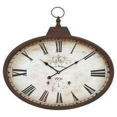 """Vintage-inspired metal wall clock with Roman numerals on a weathered face.  Product: Wall clockConstruction Material: MetalColor: Weathered brownFeatures:  Will complement any settingLightweight Accommodates:  Batteries - not includedDimensions: 20"""" H x 24"""" W x 2.5"""" D"""