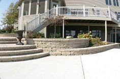 Stairway and retaining wall tackles the elevation change and gives more space for outdoor living, constructed with Versa-Lok hardscape materials.