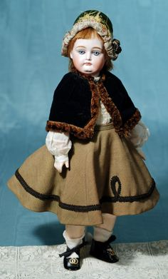 """VERY POUTY KESTNER BISQUE DOLL WITH RARE KID AND COMPOSITION BODY. Marks: 6. 16"""". Bisque swivel head on bisque shoulderplate, blue sleep eyes, unusual Kestner body with torso, upper arms and legs of kid, lower arms and legs of composition with ball joints, antique black velvet cape, cotton blonde, brown skirt and velvet bonnet, newer black shoes. Commentary: Wonderful earliest Kestner face has fine quality bisque and decoration; body is illustrated in Foulke's Kestner doll book."""