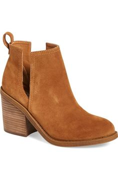 Bold side cutouts and a blocky stacked heel further the of-the-moment look of this streetwise bootie cast in nubuck leather.