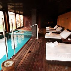 Day beds by the indoor spa pool. Relaxing atmosphere at the Spa of Hotel Son Brull in Pollensa, Mallorca.