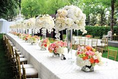 White tall glass centerpieces with Hydrangea tulips roses and white hanging orchids