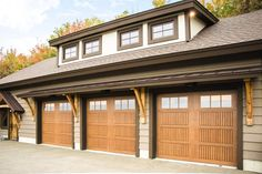 Faux wood garage doors that have the appearance of wood but are made with a fiberglass exterior for a longer lasting garage door with less maintenance. | Click image to learn more about our Model 9800 garage doors | This specific door is a Sonoma panel design with a natural oak stained finish.
