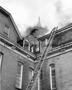Fire at T.C. State Hospital, a ladder leaning on the side of the building, a man jumping across the roof. History Center of Traverse City.