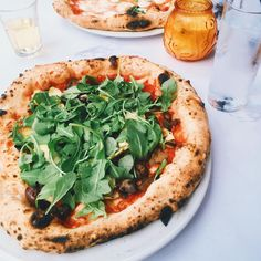 Pizza for lunch  topped with red sauce, mushrooms, artichokes, olives, + arugula