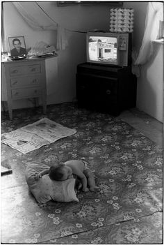 William Gale Gedney     Leaning On Pillow, Baby Sleeps On Carpeted Floor; Television in Background, Kentucky      1971